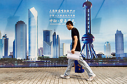 Man walking on street past billboard advertising new property development in Pudong finance district of Shanghai China