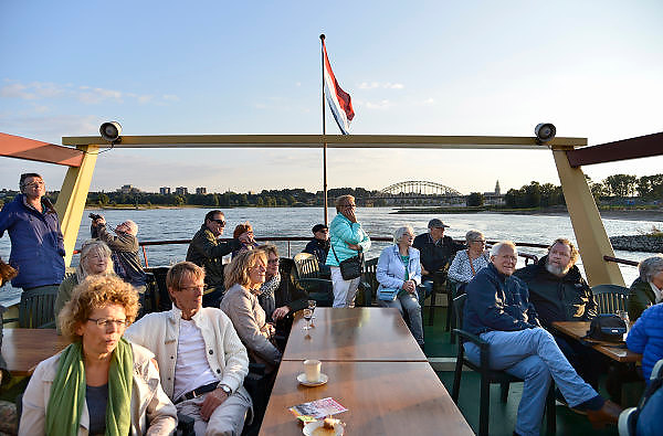 Nederland, Nijmegen, 11-9-2014Aan de overkant van de Waal bij Lent wordt druk gewerkt aan het creeren van een nevengeul in de rivier om bij hoogwater een betere waterafvoer te hebben. Het is een omvangrijk project waarbij onder meer de pijlers van het spoorviaduct een bredere basis moeten krijgen omdat die straks in de loop van het water staan. Ook de n325 die vanaf de Waalbrug naar Arnhem loopt moet over 400 meter opnieuw worden aangelegd omdat het talud vervangen wordt door pijlers. De weg wordt via een bypass omgeleid. Het dorp veurlent komt op een kunstmatig eiland te liggen. Inmiddels begint de nieuwe kade aan de noordkant van deze geul vorm te krijgen. Ruimte voor de rivier, water, waal. In de nieuwe dijk wordt een drempel gebouwd die stapsgewijs water doorlaat en bij hoogwater overloopt. Measures taken by Nijmegen to give the river Waal, Rhine, more space to flow during highwater and to prevent the risk of flooding. Room for the river. Reducing the level, waterlevel. Op een boot kan via de toegang bij de nieuwe stadsbrug de Oversteek een stukje de geul, kreek, ingevaren worden. De journalist Rob Jaspers van de regionale krant de gelderlander houdt met groot succes al maanden rondvaarten met zijn gesproken begeleiding voor belangstellenden.Foto: Flip Franssen/Hollandse Hoogte