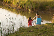 A woman and toddler share a quiet moment on the edge of a pond