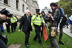 """© Licensed to London News Pictures. 07/10/2019. London, UK. Extinction Rebellion activists are seen being detained by police after spray painting at words """"LIFE NOT DEATH FOR MY GRANDCHILDREN"""" on the wall of The Treasury in Westminster. Activists plan to converge on Westminster blockading roads in the area for at least two weeks calling on government departments to 'Tell the Truth' about what they are doing to tackle the Emergency. Photo credit: Ben Cawthra/LNP"""