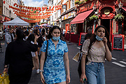 With many people and families staying in the UK for their Summer break during the school holidays, a large number of domestic tourists, who may normally have been travelling abroad, have decended on the capital to see the sights, as seen here under the Chinese lanterns on Gerrard Street in Chinatown on 10th August 2021 in London, United Kingdom. Following the Coronavirus / Covid-19 health scare of the last two years, and with some travel restrictions still in place, more people have chosen a staycation which is a holiday spent in ones home country rather than abroad, or one spent at home and involving day trips to local attractions.