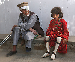 KABUL,AFGHANISTAN - SEPT. 11: An Afghan girl with polio and a man who lost his leg  learn to walk with at an ICRC hospital in Kabul, Afghanistan September 11,2002. While Americans are remembering the attack on the World Trade Center  one year ago today, most Afghans are trying to forget the decades old war which killed more than a million people here in Afghanistan. (Photo by Ami Vitale/Getty Images)