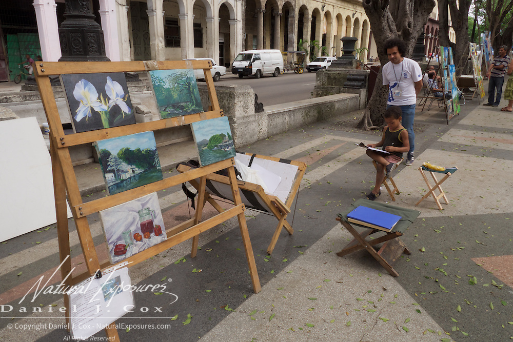 A very young artist and his older friend working on their craft on the Prado in Havana, Cuba.