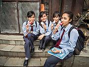 30 JULY 2015 - KATHMANDU, NEPAL:    Nepalese school girls eat ice cream treats in the courtyard at Shree Gha stupa, a large Buddhist stupa near Durbar Square in Kathmandu.   PHOTO BY JACK KURTZ