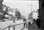 """15/06/1963.06/15/1963.15 June 1963.Dublin tenements evacuated at Fenian Street..The scen this morning at Fenian Street, Dublin as families living in century  old tenement houses evacuate their homes at No.9 and 10, and await the expected collapse of the buildings..""""The houses are only a few doors away from those which collapsed on Wednesday last, killing two schoolgirls. Most of the families spent the night on the roadside with their furniture..Dublin Tenements, collapsing in various parts of the city recently has caused a stste of emergency. Corporation officals are franticly trying to find alternative accomodation for hundreds of families occuping condemned or dangerous houses."""""""