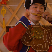 A young Mongolian musician plays a mouth harp in a home in Ulaanbaatar that he and his father have decorated to look like a ger (yurt).