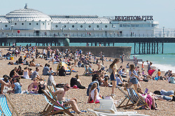© Licensed to London News Pictures. 01/09/2016. Brighton, UK. Members of the public relax in the sun on the beach in Brighton on the first day of Fall. Photo credit: Hugo Michiels/LNP