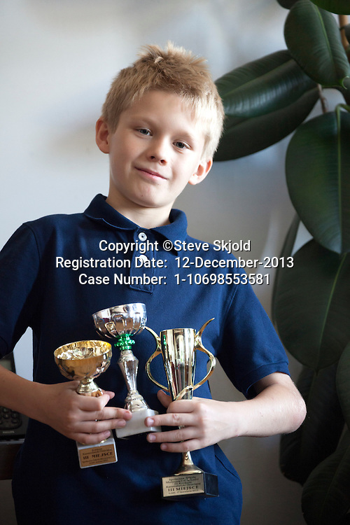 Polish boy age 10 proudly holds his trophies for violin playing at a Concert of Chamber Music for Children. Lodz Central Poland