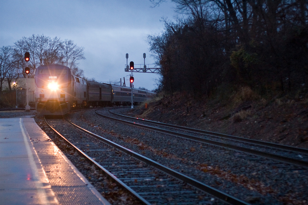 With headlight shining, an Amtrak train pulls into the Charlottesville, Virginia station bound for Washington D.C. early in the morning.
