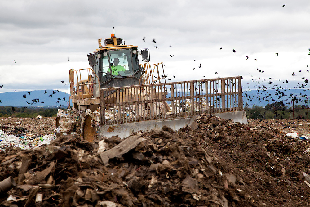 Bulldozer moves daily cover soil on top of open cell of sanitary landfill