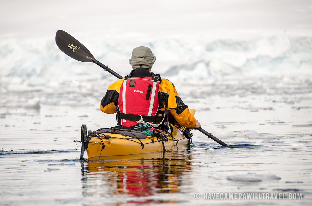 A kayaker paddles through light brash ice in calm waters at Cuverville Island on the Antarctic Peninsula.