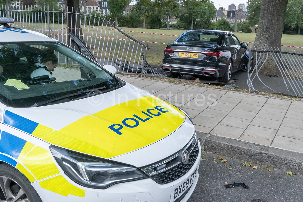 In the aftermath of a crashed Audi car that has crashed through railings of Ruskin Park, a public space in Herne Hill, on 21st August 2020, in London, United Kingdom. The car was seen speeding through Ferndene Road, a residential street in Lambeth, bouncing off a speed hump at great speed, colliding with a parked car and crashing through railings. The two occupants left the scene on foot and no-one was injured. Two males were later detained.