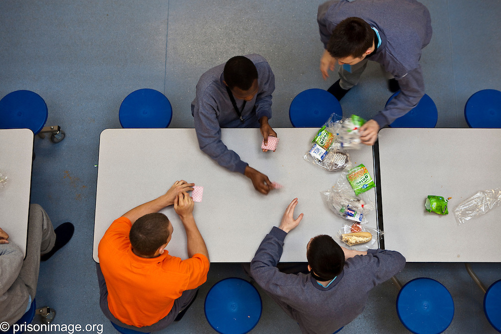 Young offenders play cards during lunch on K wing of the YOI. HMP & YOI Littlehey. Littlehey is a purpose build category C prison.