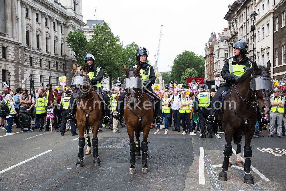 London, UK. 9th June, 2018. Mounted police officers stand in front of anti-fascists protesting against the far-right March for Tommy Robinson in Parliament Street.