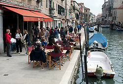 Small pavement cafe beside canal in Cannaregio district of Venice Italy