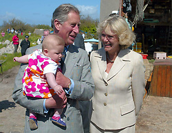 File photo dated 20/05/05 of the Prince of Wales cuddling five-month-old Charlotte Bond as his wife, the Duchess of Cornwall looks on, on the island of St Agnes in the Scilly Isles. Charles and Camilla are celebrating their 15th wedding anniversary on Friday, after they were reunited on Monday when the 72-year-old duchess came out of a 14-day self-isolation on the Balmoral estate in Aberdeenshire.