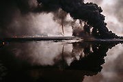 Kuwait oil well fires. Al Burgan field. Tornados of smoke reflected in oil lake.