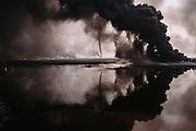 Kuwait oil well fires. Al Burgan field. Tornados of smoke reflected in oil lake.