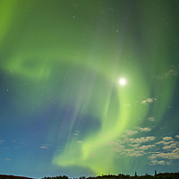 The full moon caught in a swirl of northern lights in Denali National Park.  This was the last night of my stay in the park, and after days of rain and clouds...the skies cleared.  It was my first time to see the aurora, and now I want to see it more.  © John McBrayer 2015