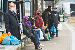 © Licensed to London News Pictures 03/03/2021. <br /> Bromley, UK. Shoppers waiting at a bus stop wearing protective masks. People out and about in Bromley High Street in South East London today during a third national coronavirus lockdown. Non-essential shops could open in weeks if the Covid-19 infection rate keeps dropping. Photo credit:Grant Falvey/LNP