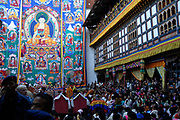 Crowds of dignitaries in formal national dress and local people watch as the giant silk applique thangka, thondrol, is unfurled in the dim early morning light before sunrise on the last day of the Trashigang festival. Crowds gather to see this building sized work of art and to gain merit from the sight. The thangka is rolled up and put away before the sunlight can damage it. Trashigang Dzong, Trashigang, Bhutan, Druk Yul. 20 November 2007