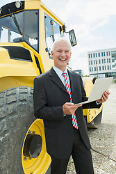 Businessman with laptop on construction site