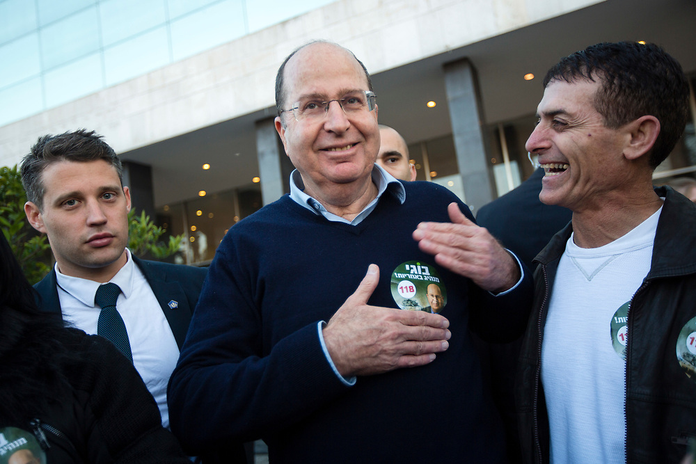 Israel's Defense Minister Moshe Ya'alon (C) interacts with Likud party activists after casting his vote during the Likud party primary elections in Jerusalem, on December 31, 2014. Likud's leader and Israel's Prime Minister Netanyahu (not pictured) is widely expected to retain the helm of the right-wing Likud party ahead of Israel's general elections in March.