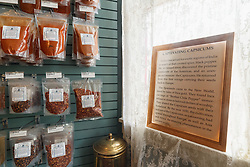 """""""Captivating Capsicums"""" story and assorted chiles and spices on display near lace window at Pendery's World of Chiles & Spices, Fort Worth, Texas USA."""