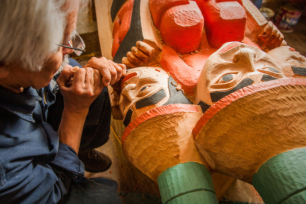 Tlingit/Haida Master Carver, Nathan Jackson, uses a small carving tool to carve details of a totem at the carving shed in Saxman, Alaska.