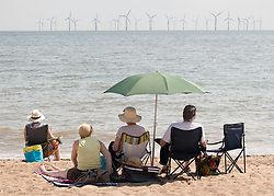 © Licensed to London News Pictures. 25/07/2019. Skegness, Lincolnshire, UK. Skegness seaside resort swelters under the summer heat. Staying in the shade and looking out to the wind turbines. Photo credit: Dave Warren/LNP