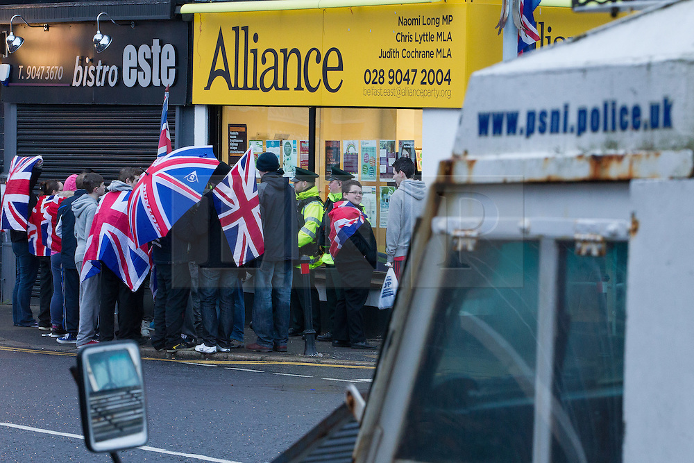 """© Licensed to London News Pictures . 11/01/2013 . Belfast , UK . Loyalist protesters stand in front of the office of the Alliance Party on the Newtownards Road in East Belfast today (11th January 2013) ahead of """" Operation Standstill """" . The protest is one of many that have been held since Belfast City Council voted to stop flying the Union flag above Belfast City Hall . Photo credit : Joel Goodman/LNP."""