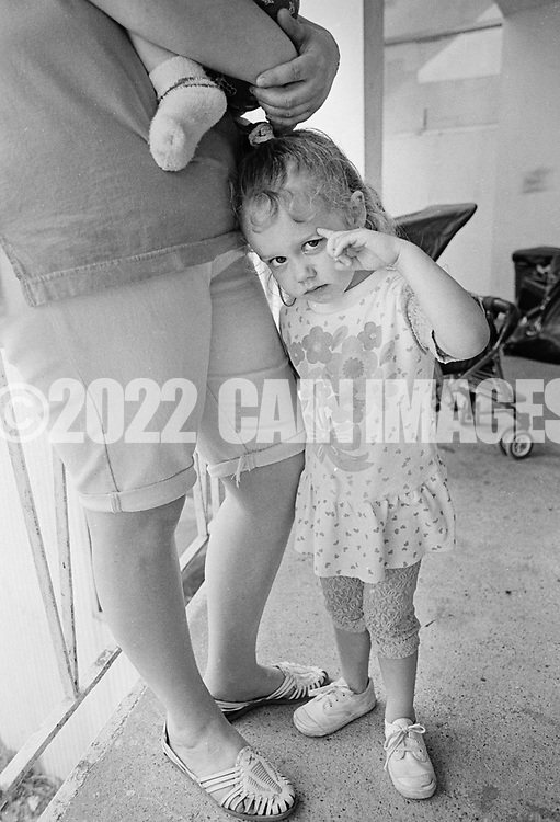 Stevie Nicole Painter, 3, clings to her mother Debbie's leg as her she holds son Brandon, 7 months at the George Washington Motor Lodge, where they are living Tuesday June 23, 1992 in Bensalem, Pennsylvania. (WILLIAM THOMAS CAIN / For The Philadelphia Inquirer)