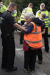 Godstone, UK. 13th September, 2021. Surrey Police officers arrest Insulate Britain climate activist Reverend Sue Parfitt who had blocked a slip road from the M25 as part of a new campaign intended to push the UK government to make significant legislative change to start lowering emissions. The activists, who wrote to Prime Minister Boris Johnson on 13th August, are demanding that the government immediately promises both to fully fund and ensure the insulation of all social housing in Britain by 2025 and to produce within four months a legally binding national plan to fully fund and ensure the full low-energy and low-carbon whole-house retrofit, with no externalised costs, of all homes in Britain by 2030 as part of a just transition to full decarbonisation of all parts of society and the economy.