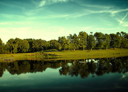 Evening Light falls of the plush green trees that surround the fishing lake in the middle of Broemmelsiek Park in Wentzville (Saint Charles County) Missouri