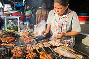 """26 SEPTEMBER 2012 - BANGKOK, THAILAND:  A street vendor grills chicken in Khlong Toey Market in Bangkok. Khlong Toey (also called Khlong Toei) Market is one of the largest """"wet markets"""" in Thailand. The market is located in the midst of one of Bangkok's largest slum areas and close to the city's original deep water port. Thousands of people live in the neighboring slum area. Thousands more shop in the sprawling market for fresh fruits and vegetables as well meat, fish and poultry.    PHOTO BY JACK KURTZ"""