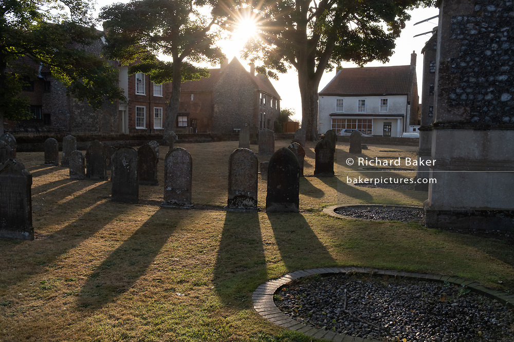 Morning sunshine and the churchyard of the Church of St. Mary the Virgin, a building funded from the wealth of the14th century local weaving industry, on 10th August 2020, in Worstead, Norfolk, England.