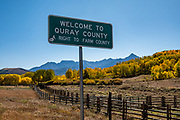 Ouray County sign at Dallas Divide, 8983 ft elevation, yellow fall colors, west of Ridgway, San Juan Mountains, Colorado, USA.