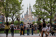Visitors walk through Walt Disney Co.s Shanghai Disneyland theme park  towards the iconic castle during a trial run ahead of its official opening, in Shanghai, China, on Wednesday, June 8, 2016. The $5.5 billion Shanghai Disneyland is one  of the most profitable Disney ventures in the world and the first theme park on mainland China.