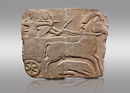 Picture & image of Hittite monumental relief sculpted orthostat stone panel. Limestone, Karkamıs, (Kargamıs), Carchemish (Karkemish), 900-700 B.C. Hunting carriage.  Anatolian Civilisations Museum, Ankara, Turkey.<br /> <br /> Two human figures; one handling the carriage, the other throwing arrows. Both figures are wearing a headdress shaped like a skullcap. The dagger at the waist of the figure throwing arrow draws attention. There is an animal between the legs of the horse having an aigrette over its head. <br /> <br /> Against a gray background. .<br />  <br /> IIf you prefer to buy from our ALAMY STOCK LIBRARY page at https://www.alamy.com/portfolio/paul-williams-funkystock/hittite-art-antiquities.html  - Type  Karkamıs in LOWER SEARCH WITHIN GALLERY box. Refine search by adding background colour, place, museum etc.<br /> <br /> Visit our HITTITE PHOTO COLLECTIONS for more photos to download or buy as wall art prints https://funkystock.photoshelter.com/gallery-collection/The-Hittites-Art-Artefacts-Antiquities-Historic-Sites-Pictures-Images-of/C0000NUBSMhSc3Oo