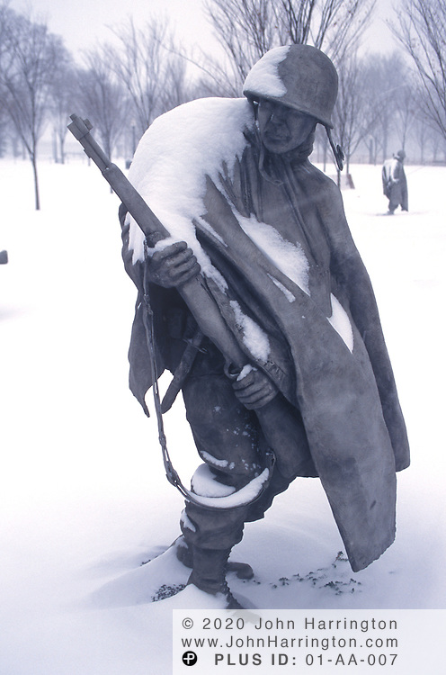 Korean War Memorial statues are covered in a light snow.