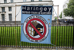 London, UK. 15th July, 2021. A Haringey Defend Council Housing banner is pictured during a protest opposite Downing Street by leaseholders and tenants living in unsafe homes. Some leaseholders are faced with crippling costs to fix safety issues and they called on the government to ensure that their homes are made safe from fire as a matter of priority, to make interim payments and cover fire safety remediation costs and to find a solution with mortgage lenders.