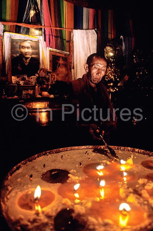A Tibetan monk tends to the yak butter lamps at Tashilunpo Monastery, Shigatze city, Tiber.