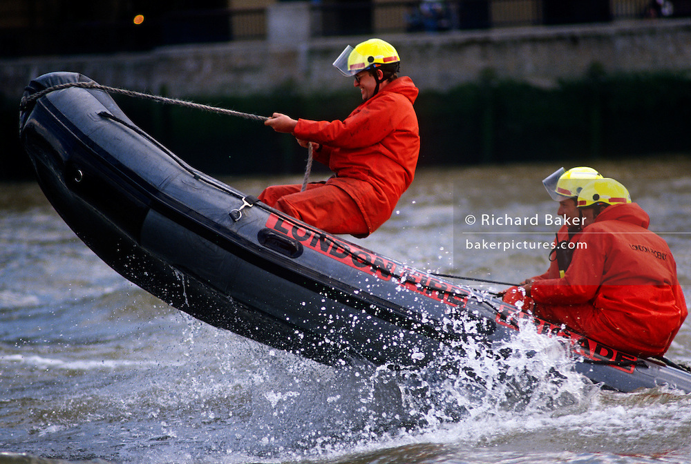 Leaping over waves, London Fire Brigade (LFB) fire fighters train on the River Thames using an inflatable dinghy