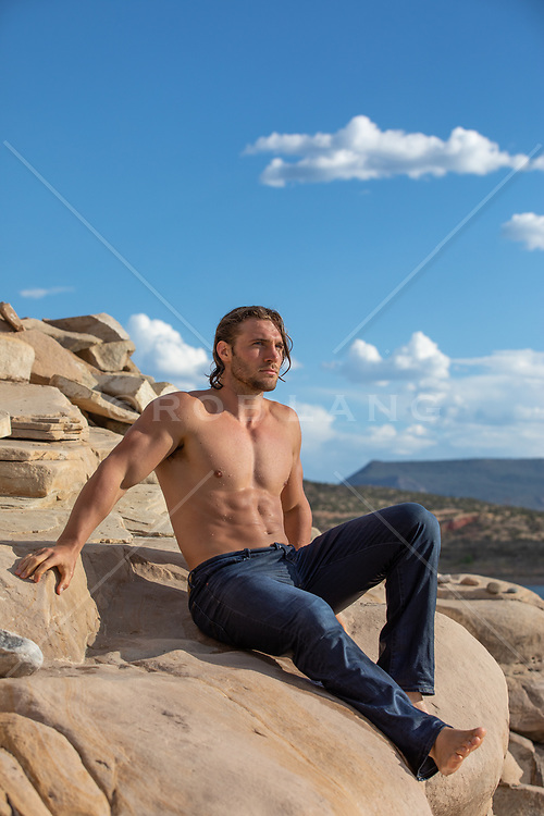 hot shirtless man in jeans on a rock formation by a lake