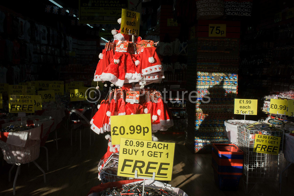 Christmas santa hats on a sunlit rack in a trinket shop on London's Oxford Street. Multiple signs for Buy One Get One Free (BOGOF) dealsare seen around the front end of the trinket shop on this busy shopping street in the capital's West End. They are almost giving these sheap products away which will almost certainly be made in Asia where Christmas is not a traditonally cultural phenomenon.