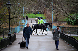 © Licensed to London News Pictures. 21/12/2016. London, UK. Mounted police officers watch over during road closures in place around Buckingham Palace in London at the time of Changing of the Guard ceremony. The extra closures have come in to place following a terrorist attack using a vehicle in Berlin.  Photo credit: Ben Cawthra/LNP