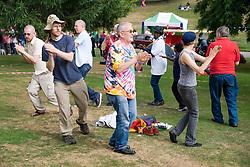 Men and women dancing in a circle at Nottingham's 2005 Gay Pride Lesbian festival; held at the Arboretum,