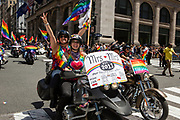 """New York, NY - 25 June 2017. New York City Heritage of Pride March filled Fifth Avenue for hours with groups from the LGBT community and it's supporters. Two women  ride a motorcycle with a sign reading """"Mrs. [heart] Mrs."""" and giving a history of the relationship, civil union, and marriage."""