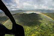 See an intense rainbow through rain-spattered windows of a helicopter flying over the island of Kauai, Hawaii, USA.