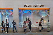 Masked shoppers queuing outside the Louis Vuitton store In London's Bond Street the last day before the second national coronavirus lockdown on 4th November 2020 in London, United Kingdom. The new national lockdown is a huge blow to the economy and for individuals who were already struggling, as Covid-19 restrictions are put in place until 2nd December across England, with all non-essential businesses closed.